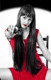 Gefährliches Mädchen mit Pistole (schwarz, weiß und rot) Stockfotografie