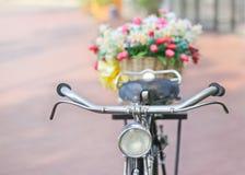 Gefälschte Blume im Korb auf Weinlesefahrrad Stockfotografie