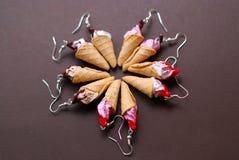 Gefälschte Miniatur-Wafe-Eiscreme-Ohrringe Jewellry-Zubehör mit unterschiedlichem Belag auf Brown-Hintergrund stockbild