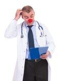 Gefälschter Doktor des Idioten, der seinen Kopf beim Ablesen verkratzt Stockfotos