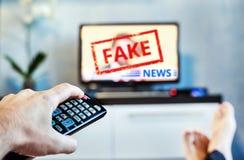 Gefälschter Nachrichten-Propaganda HOKUSPOKUS-politisches Fernsehinternet-soziales junger Mann, der im Fernsehen den gefälschten  stockbilder