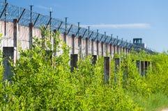 Gefängnismauer und scharfe Drahtwiderhaken umwickelt Stockfotos