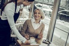 Gefühl der eleganten Frau dankbar beim Erhalten ihres Kaffees auf Cafeteria stockfoto