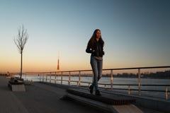 Gefühl der jungen Frau überzeugt während eines Lebensstilwegs entlang dem Fluss Daugava bei einem Sonnenuntergang lizenzfreie stockfotos