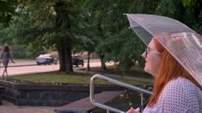Gefühl des fetten Ingwermädchens mit Gläsern alking herauf kleine Treppe im Park im regnerischen Wetter und hält Regenschirm stock video footage