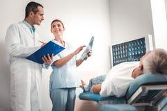 Gefühl mit zwei behauptete Berufsdoktoren, nachdem es Ergebnisse des Röntgenstrahls erhalten hatte lizenzfreie stockfotografie
