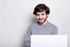 Gefühle, Mensch, moderne Technologien und Lebensstilkonzept Glücklicher attraktiver junger bärtiger Kerl, der freie drahtlose Ver stockfotografie