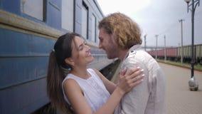 Gefühlfreude am glücklichen Umarmungsmann und -lachen der jungen Frau nahe Bahnwagen auf Bahnhof nach Trennung stock footage
