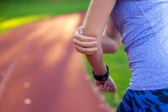 Gefühlsschmerz der jungen Frau in ihrem Ellbogen während des Sporttrainings an St. lizenzfreies stockfoto