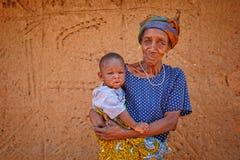 GEFÜLLTE MAISMEHLTASCHE, GHANA-ï ¿ ½ am 24. März: Nicht identifizierte alte Afrikanerinholding Stockfotografie