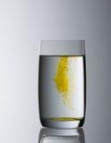 Gefülltes Wasserglas mit gelber Steigung Lizenzfreie Stockfotografie