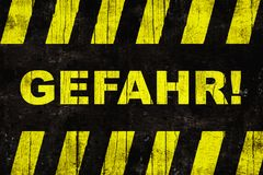 """Gefahr auf Deutsch, Warnzeichen """"danger† Textes mit den gelben und schwarzen Streifen Lizenzfreies Stockbild"""