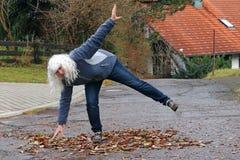 Gefahr im Herbst Eine Frau gleitet auf einer Straße auf nass Blättern lizenzfreies stockbild