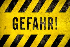 GEFAHR! no alemão, no texto do sinal de aviso do perigo com as listras amarelas e pretas pintadas sobre o fundo da textura do cim fotografia de stock royalty free