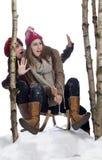 Gefahr: zwei junge Frauen auf einem Schlitten Stockbilder