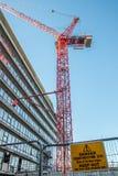 Gefahrenbaustelle halten Zeichen mit rotem Kran über Stadt ab Lizenzfreie Stockfotos