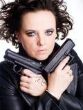 Gefahrenfrau, die zwei Gewehren anhält Stockfotografie