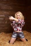 Gefahrensexy Frau mit Revolver über Stapel von Strohbeschaffenheit backg Stockfotos