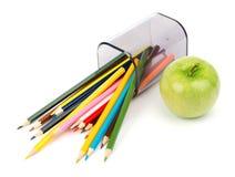 Gefallene Bleistiftschale mit Zeichenstiften und grünem Apfel Stockfotografie