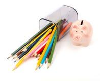 Gefallene Bleistiftschale mit Zeichenstiften und rosa Sparschwein Lizenzfreies Stockfoto