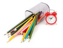 Gefallene Bleistiftschale mit Zeichenstiften und rotem Wecker Lizenzfreies Stockfoto