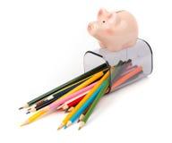 Gefallene Bleistiftschale mit Zeichenstiften und Sparschwein Stockfotografie