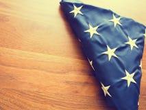 Gefaltete amerikanische Flagge auf einem Holztisch Stockbild