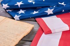 Gefaltete Flagge von USA und von altem Buch stockbild