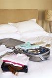 Gefaltete Kleidung und verpackter Koffer auf Bett Lizenzfreies Stockbild