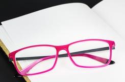 Gefaltete rosa Gläser auf Buch Lizenzfreie Stockfotos