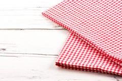Gefaltete rote karierte Tischdecke auf weißem hölzernem Brett Lizenzfreie Stockbilder