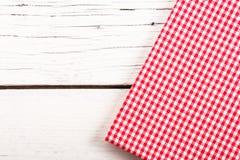 Gefaltete rote karierte Tischdecke auf weißem hölzernem Brett Stockfotografie