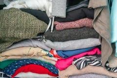 Gefaltete Strickjacken und Kleider der Garderobe einer Frau in einem Wandschrank Schilderung des Überflusses, der Bedarf an der  lizenzfreies stockfoto