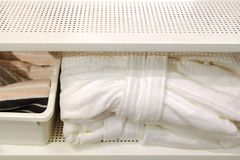 Gefaltete Tücher, Teppichpantoffel und Bademäntel auf einem Regal eines Wandschranks in einem Hotel lizenzfreies stockfoto