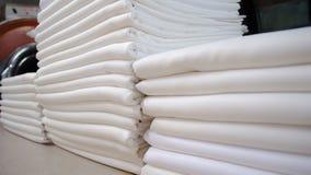 Gefaltete weiße Stoffe in einer Wäscherei stockfoto