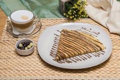 Gefalteter Krepp, russischer Blini mit Schokoladensoße auf weißer Platte mit Cappuccino und Dragees mit Gewebebeutel und gelben B Stockfotos