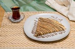 Gefalteter Krepp, russischer Blini mit Schokoladensoße auf weißer Platte diente mit türkischem Tee Lizenzfreie Stockfotografie