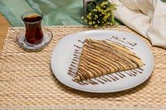 Gefalteter Krepp, russischer Blini mit Schokoladensoße auf weißer Platte diente mit türkischem Tee mit Gewebebeutel und gelben Bl Lizenzfreie Stockfotografie