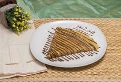 Gefalteter Krepp, russischer Blini mit Schokoladensoße auf weißer Platte mit Gewebebeutel und gelbe Blumen Stockfotos