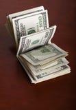 Gefalteter 100 US$-Rechnungs-Stapel auf Brown-Hintergrund Stockfoto