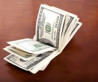 Gefalteter 100 US$-Rechnungs-Stapel auf Brown-Hintergrund Stockfotos