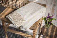 Gefaltetes weißes Tuch mit Brown-Fischgrätenmuster-Design auf quadratischem Sidet Lizenzfreies Stockfoto