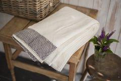 Gefaltetes weißes Tuch mit schwarzem Fischgrätenmuster-Design auf quadratischem Sidet Stockfoto