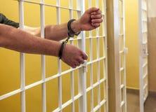 Gefangener in den Handschellen zugeschlossen in eine Zelle. Lizenzfreie Stockbilder
