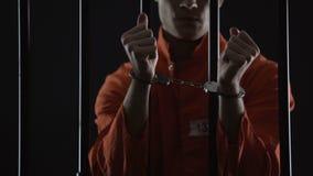 Gefangener in der orange Uniformvertretung fesselt mit Handschellen, schaut verärgert und enttäuscht stock video footage