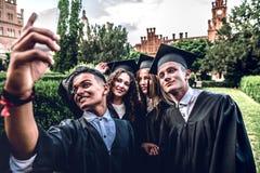 Gefangennehmen eines glücklichen Momentes Herstellung des Fotos von Absolvent in den Umhängen, die nahe Universität stehen und Lä lizenzfreies stockbild