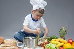 Gefascineerd Kaukasisch Little Boy die werken met zwaait in het Koken van Hoed stock foto's
