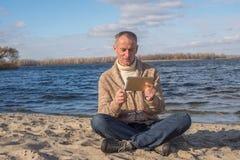 Gefascineerde mens, die gebruikend zijn tablet terwijl relaxin terloops dragen Stock Fotografie