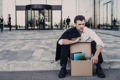 Gefeuerter Geschäftsmann, der auf Straße sitzt Stockbild