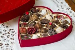 Geöffneter roter Herz Valentinsgruß-Pralinekasten mit unterschiedlichem ind Stockbild